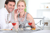 An elegant couple having dinner and smiling at us. — Stock Photo