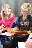 Two women discussing work in a folder — Stock Photo