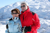 Older ski couple on a mountain — Stock Photo