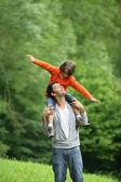Küçük çocuk babasının omuzlarında oturdu — Stok fotoğraf