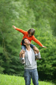 Little boy sat on father's shoulders — Stockfoto