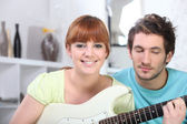 Red-haired girl playing guitar in bedroom with boyfriend — Stock Photo