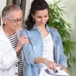 Stock Photo: Young woman ironing for an elderly lady