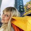Blonde carrying shopping bags on shoulder - Stock Photo