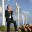 Businessman talking on his mobile phone by a row of wind turbines - Stockfoto