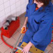 Female plumber sawing pipe - Stock Photo