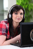 Woman listening to her laptop through headphones — Stock Photo