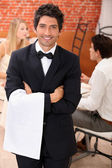 Well dressed waiter facing the camera, behind a couple is dining at restaur — Stock Photo