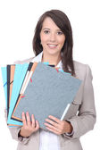 Female office worker with a pile of paperwork — Stock Photo