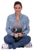 Woman sitting cross-legged and holding an electric screwdriver — Stock Photo