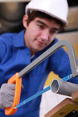 Young man is cutting a pvc pipe with a saw — Stock Photo