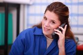 Young woman in blue overalls on the telephone in a depot — Stock Photo