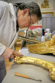 Man restoring golden picture frame — Stock Photo