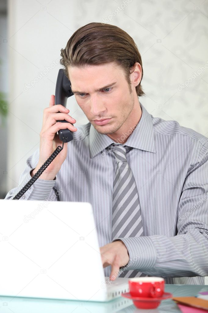 Young businessman on the phone while using his laptop — Stock Photo #8694910