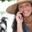 Woman wearing a straw hat talking on her mobile phone — Stock Photo