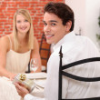 Couple in restaurant with present - Stock Photo