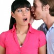 Young man whispering a secret into a woman's ear — Stock Photo
