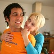 Couple stood hugging in the kitchen — Stock Photo #8753798