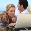 Wife working on laptop on the beach. — Stock Photo