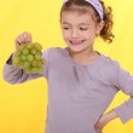 Little girl holding grapes — Stock Photo