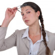 Curious businesswoman lifting glasses — Stock Photo #8755704