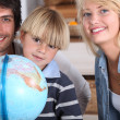 A little boy and his parents smiling near a globe — Stock Photo