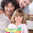 Couple playing a stacking game with their daughter — Stok fotoğraf