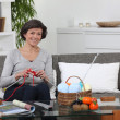 Stock Photo: Womsitting on settee knitting