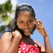 Beautiful African woman on vacation talking on her cell — Stock Photo