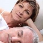 Mujer tendida junto a su esposo durmiendo — Foto de Stock