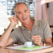 Stock Photo: Senior having expresso while talking on his cellphone