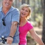 hombre y mujer en una bicicleta en el bosque — Foto de Stock