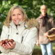 Mature woman in woods with husband showing chestnuts — Stock Photo #8757884