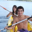Young couple kayaking down a river - Stock Photo