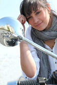 Woman looking into the wing mirror of her moped — Stock Photo