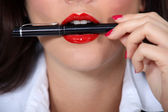 Woman with pen in mouth — Stock Photo