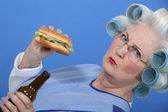 An old lady enjoying a burger and a beer. — Stock Photo