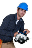 A construction worker with a circular saw. — Stock Photo