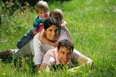 Family laying together in the park — Stock Photo
