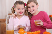 Little girls squeezing oranges — Stock Photo
