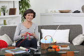 Woman sitting on settee knitting — Stock Photo