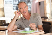 Senior having an expresso while talking on his cellphone — Stock Photo