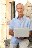 Grey haired man sat on stone wall with laptop — Stock Photo