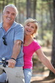 Man and woman riding a bike in the forest — Stock Photo