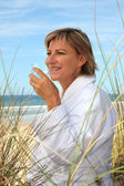 Woman drinking a glass of water on a sand dune — Stock Photo