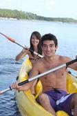 Giovane coppia kayak lungo un fiume — Foto Stock