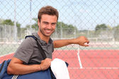 Man with sports bag stood by clay tennis court — Stock Photo