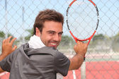 Smiling male tennis player standing outside a municipal court — Stock Photo