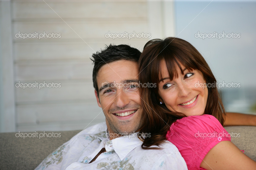 Cheerful couple sitting on a sofa — Stock Photo #8753773
