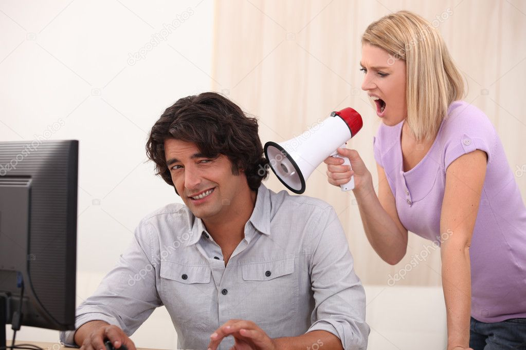 A man doing computer and a woman yelling on him with a megaphone  Stock Photo #8754964